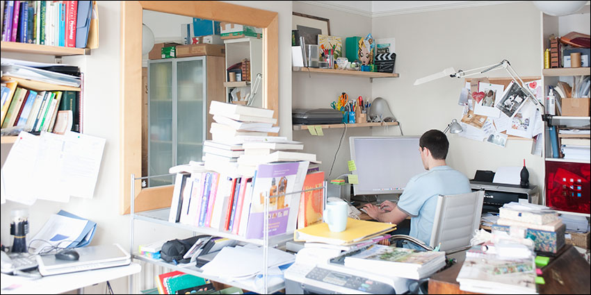 Man in cluttered home study