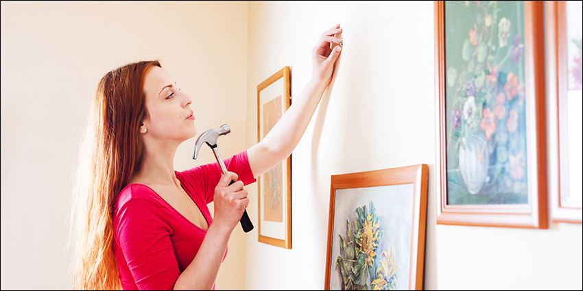 Woman hanging pictures